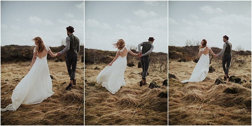 Bride and groom walking hand in hand as wind blows the bride's dress and hair