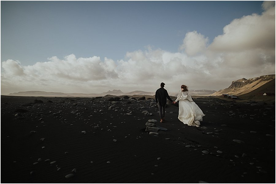 Iceland Wedding with Bride and groom walking hand in hand along the black beach at Vik by Wild Connections Photography