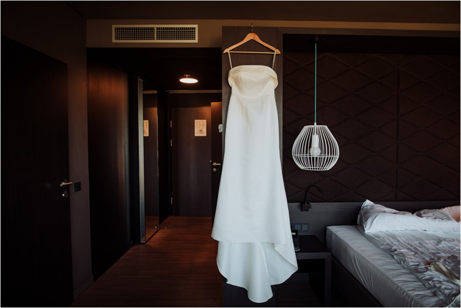 Kelly's wedding dress hangs in her room in the Adlers hotel in Innsbruck by Wild Connections Photography