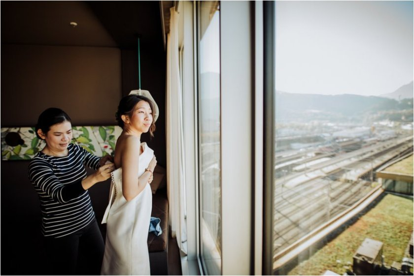 Bride Kelly puts on her dress in her hotel room in the Adlers Hotel in Innsbruck by Wild Connections Photography