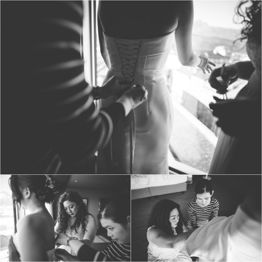 The bridesmaids help Kelly lace up her wedding dress in her hotel room in the Adlers hotel in Innsbruck by Wild Connections Photography