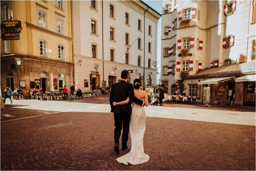 Kelly and Arik walk across the Altstadt in Innsbruck after their innsbruck wedding by Wild Connections Photography
