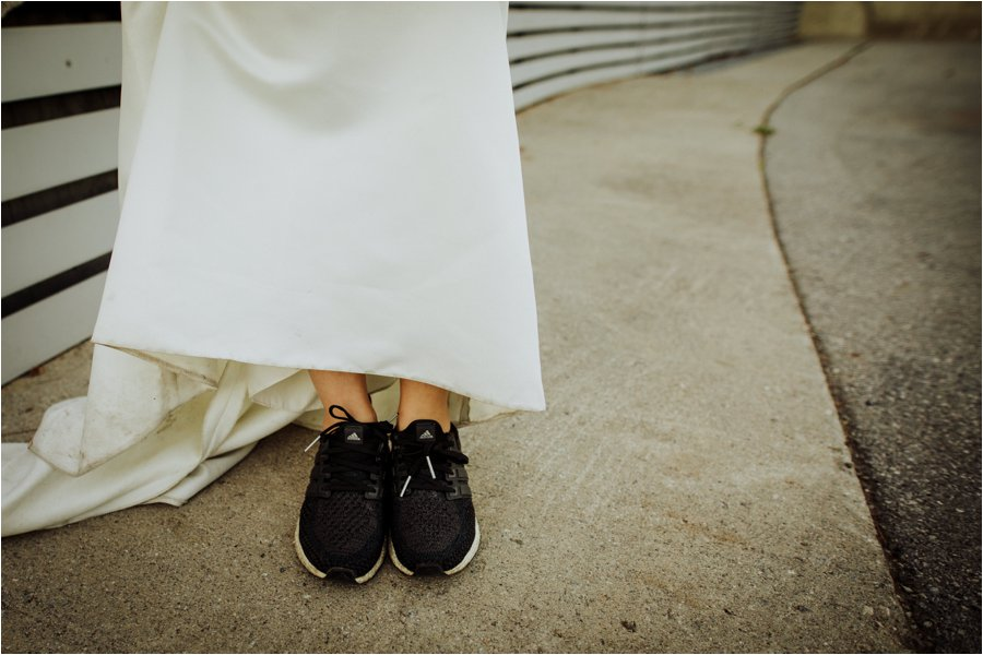 Kelly wears her adidas trainers under her wedding dress by Wild Connections Photography