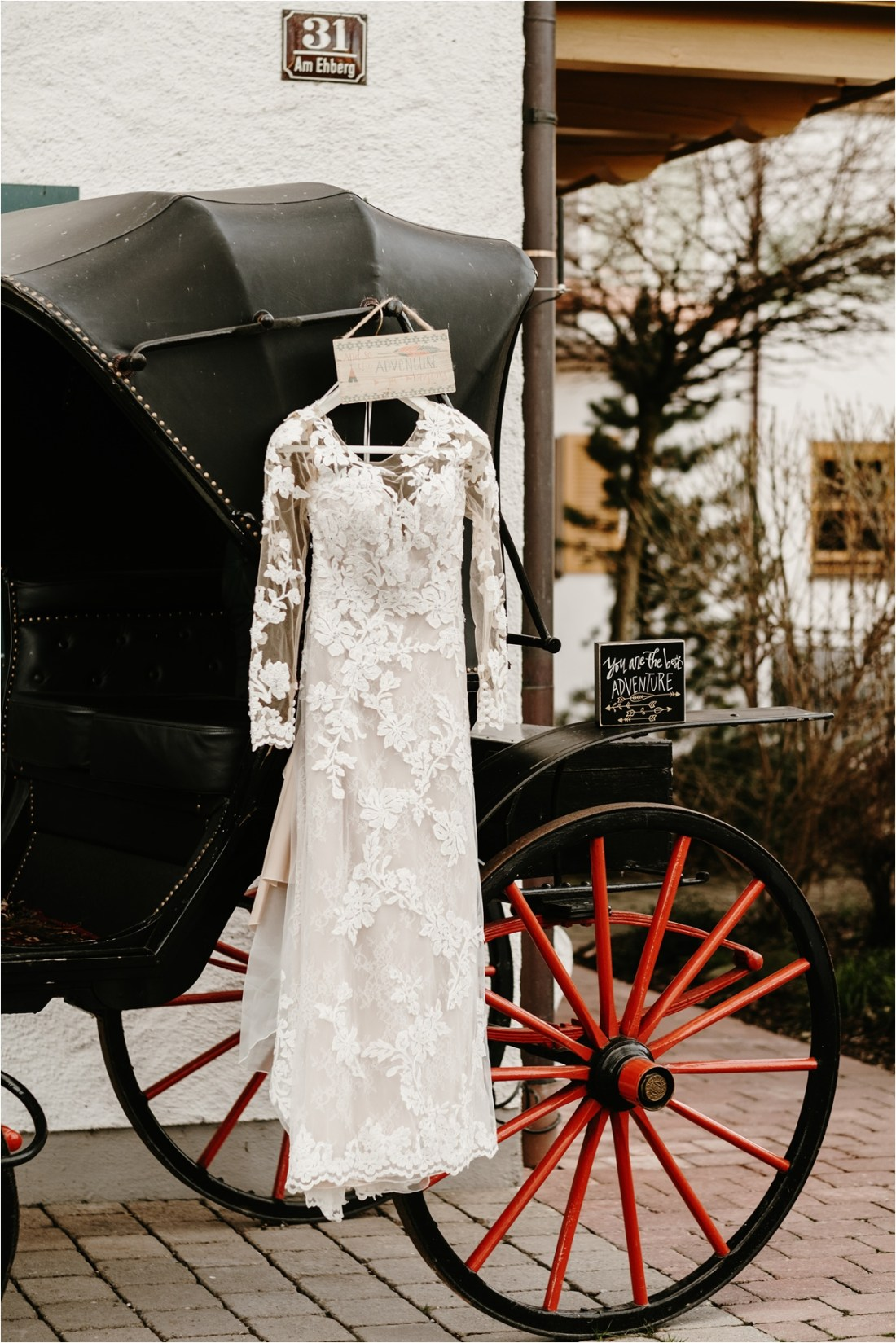Pronovias wedding dress hangs outside the venue for this LGBT elopement in the Bavarian Alps. Photo by Wild Connections Photography