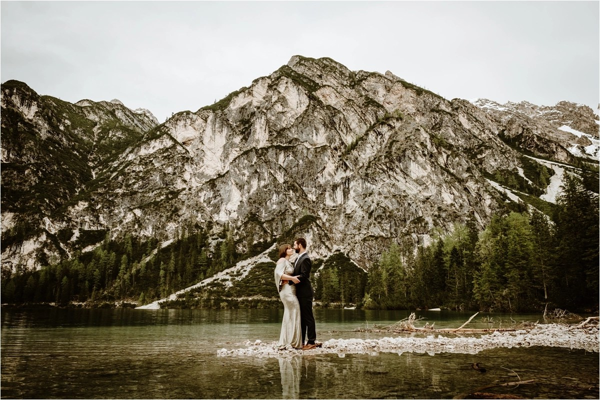 An after-wedding celebration at Lake Braies in the Italian Alps with a gold wedding gown. Photo by Wild Connections Photography