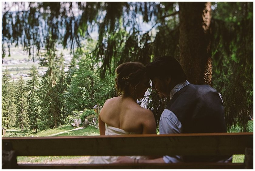 Couple sit on a bench looking over the mountains after their Austrian elopement by Wild Connections Photography