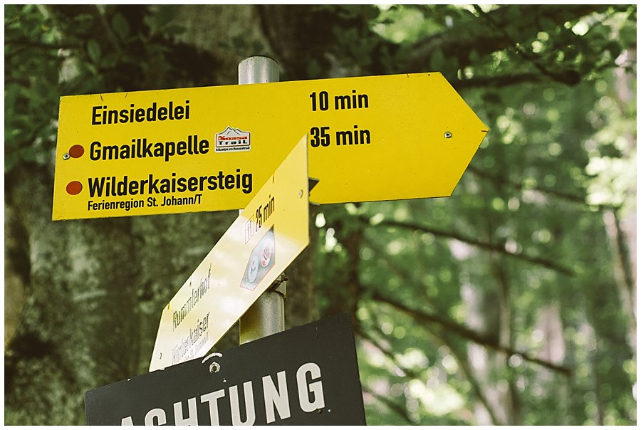 St Johann in Tirol Elopement a hiking trail sign in the woods by Wild Connections Photography