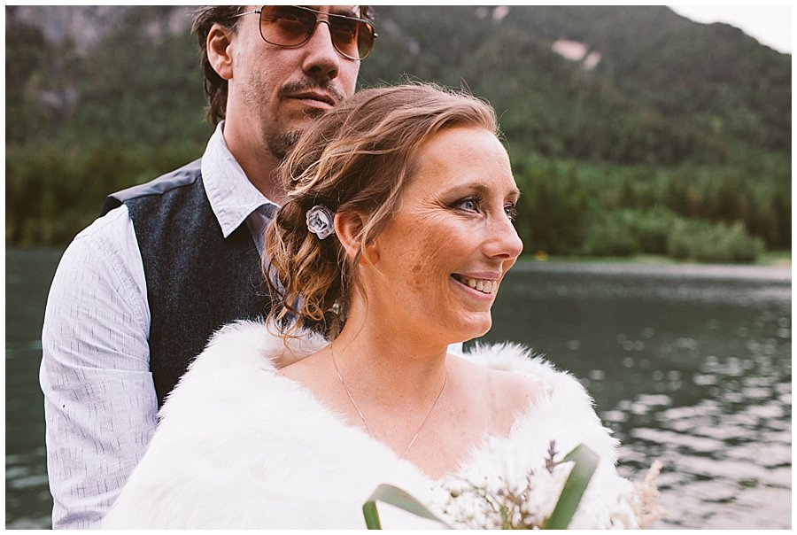 St Johann in Tirol Elopement Nikki and Chris embrace by a mountain lake by Wild Connections Photography