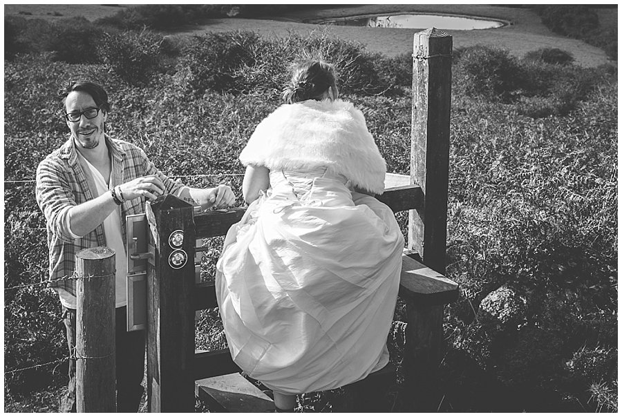 Wedding with Rescue Dogs - Black and white photo of husband and wife crossing over a stile by Wild Connections Photography