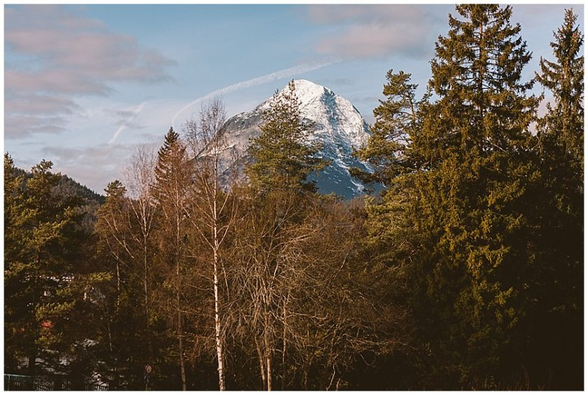 Seefeld Wedding Green trees with a snow covered mountain peak in the background by Wild Connections Photography