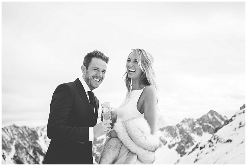 Steph and Lee start laughing holding champagne glasses with mountains in the background