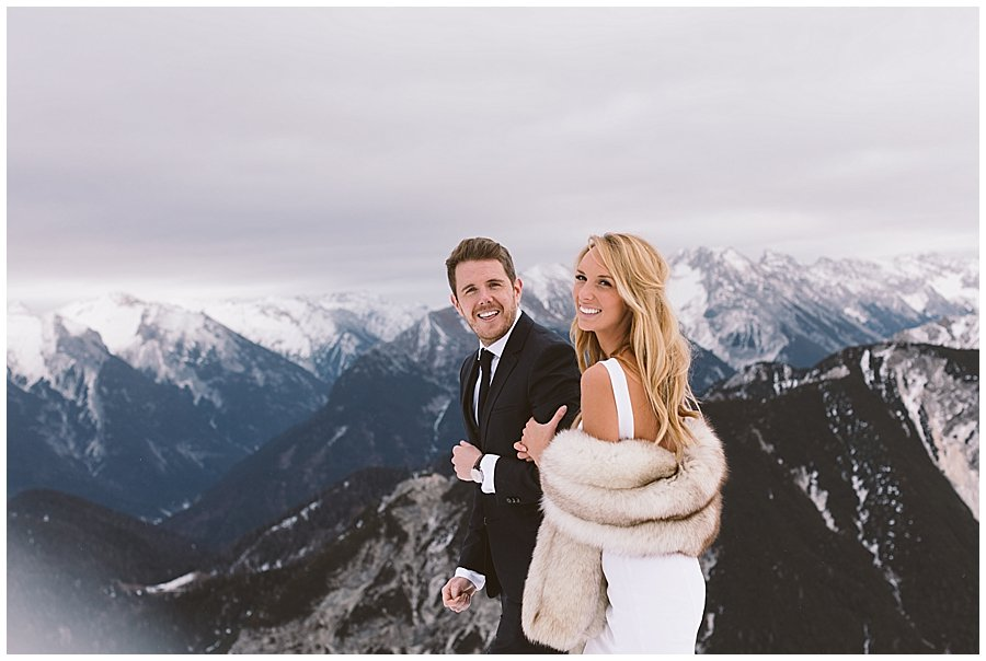 Steph and Lee smile and turn to look at the camera with dark clouds and mountains in the background behind them
