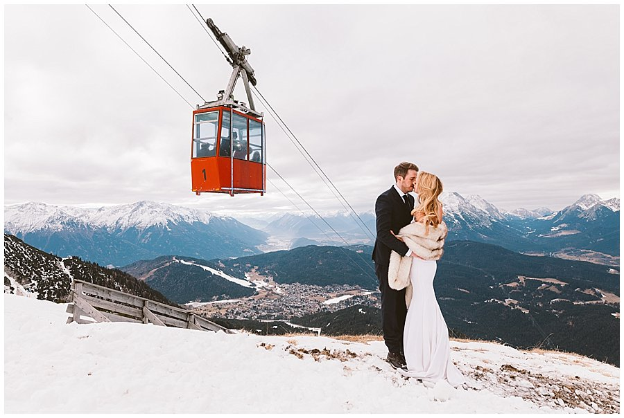 Seefeld Wedding bride and groom kiss under the cable car which transports guests up the ski slope by Wild Connections Photography