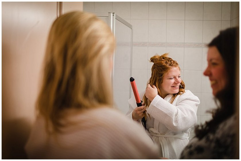 Bridesmaid curls hair in hotel bathroom