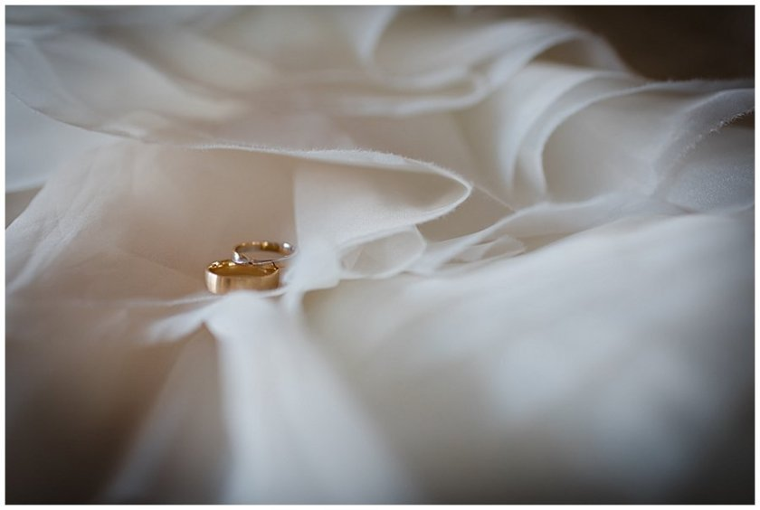 Gold wedding rings lay on the fabric of the wedding dress