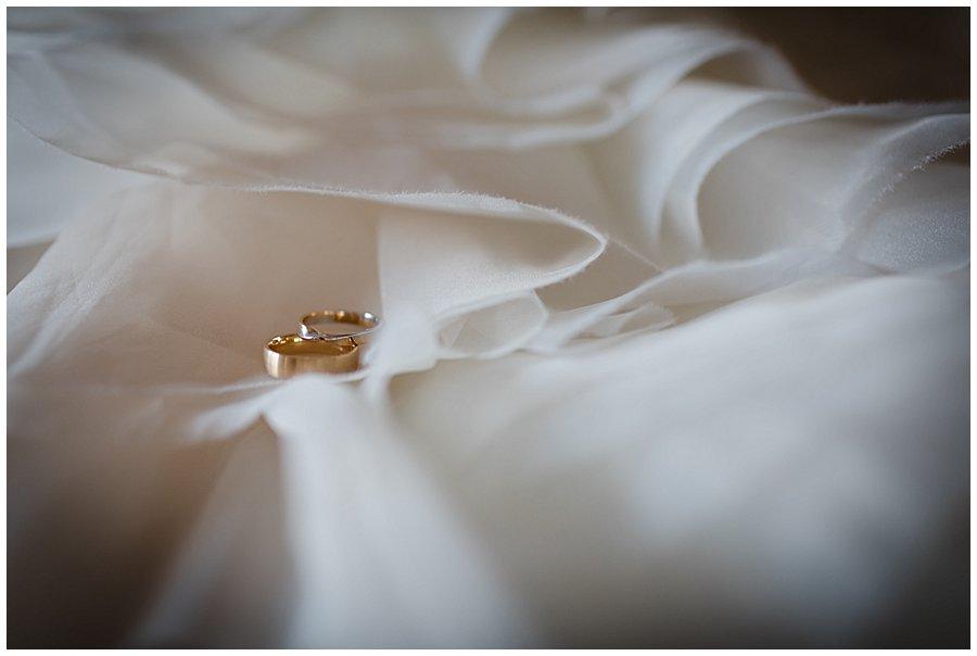 Wedding rings sit in between the ruffles of a Mori Lee wedding dress