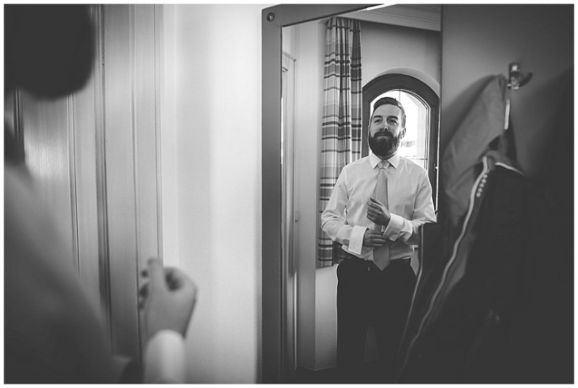 The groom Dan getting dressed in front of a mirror