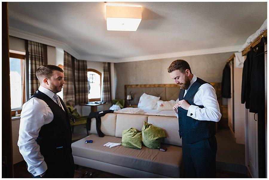 The groom Dan buttoning up his tweed waistcoat