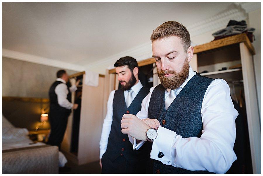 The groom Dan putting on his watch