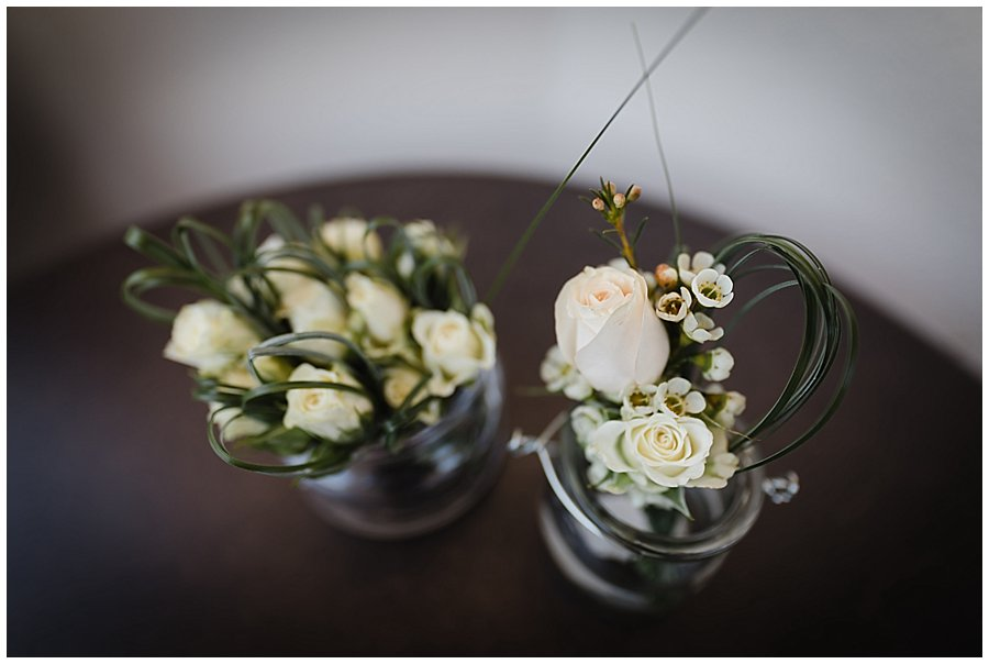 The men's buttonholes sit in glasses on the table