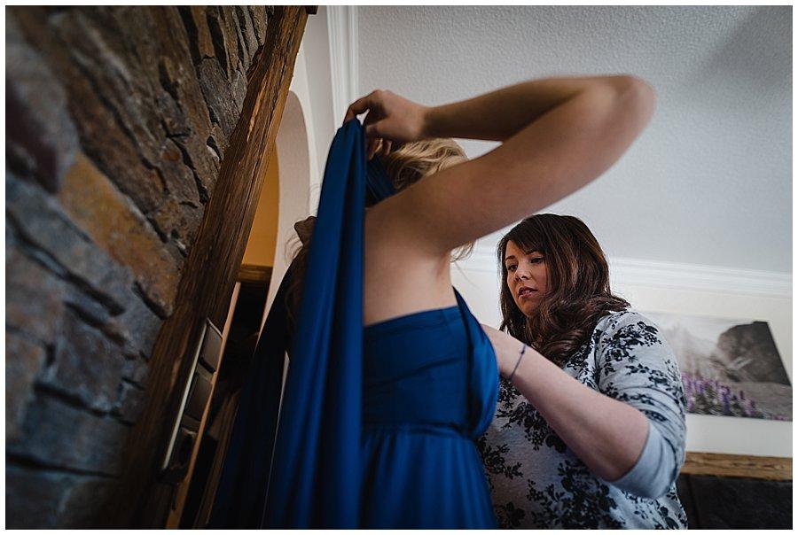 The bride Bec helps bridesmaid Robyn tie her bridesmaids dress