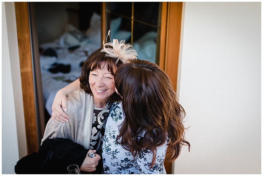 The mother of the bride arrives and gets a kiss from her daughter