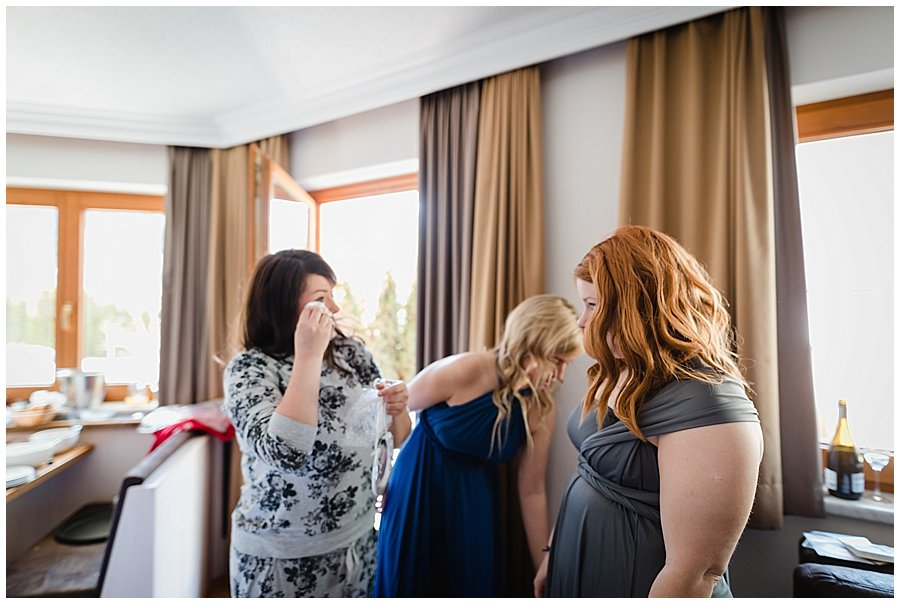 The bride Bec wipes away a tear as she shares an intimate moment with her bridesmaids