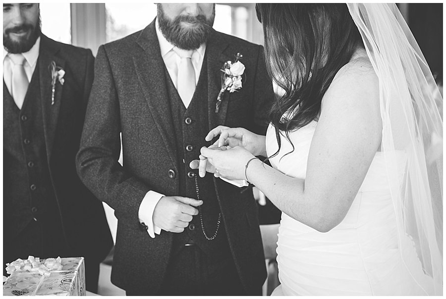 Close up of Bec putting a ring on Dan's finger