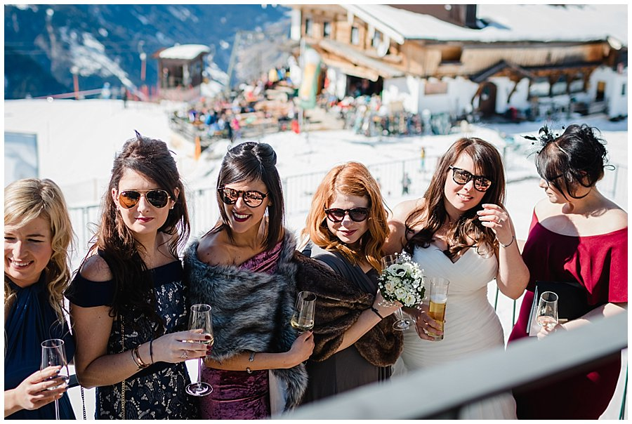 The girls drink on the reception terrace in the sunshine, wearing sunglasses