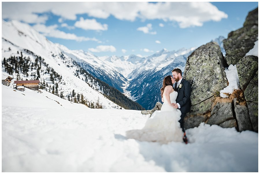 The bride and groom leaning against a rock in the snow with a mountain valley in the background