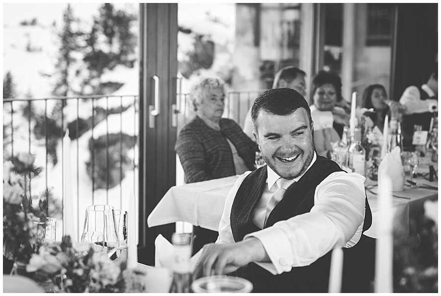 the best man laughs as he sits at the table