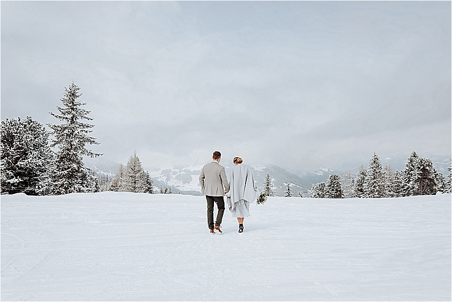 Winter mountain elopement in Mayrhofen Austria by Wild Connections Photography couple walk away in the snow with the mountains behind them