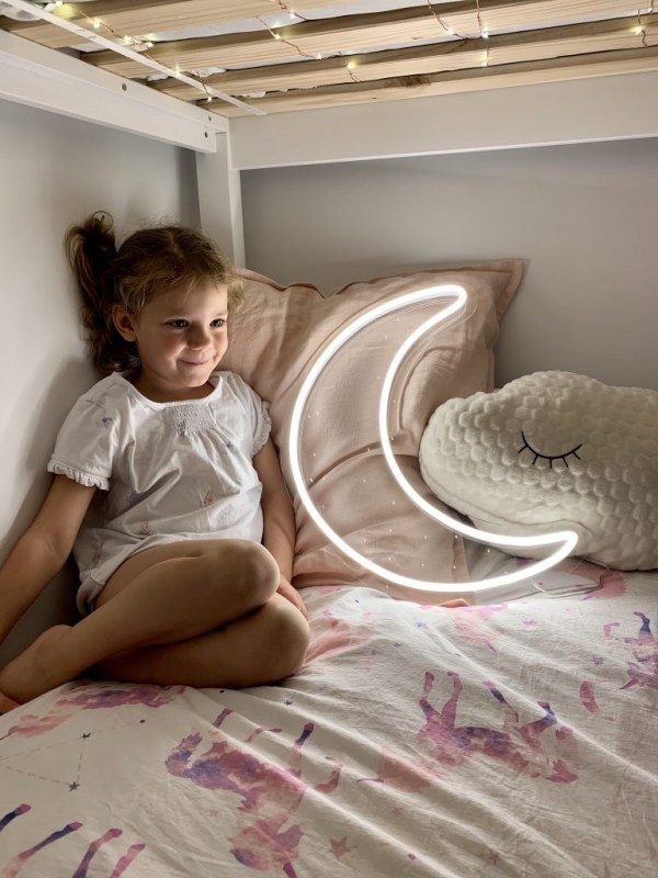 girl smiling with neon white moon light on bed