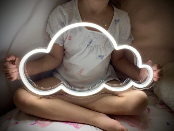 Close up of girl holding neon cloud light