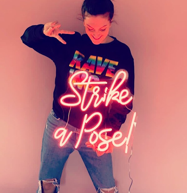 Girl posing with Strike a Pose! Neon sign