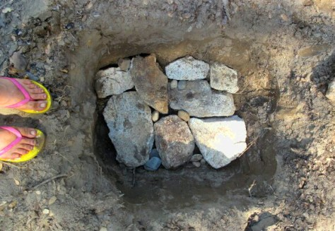 To begin constructing a steam pit, lay flat rocks to cover the base of a pit about a foot deep.