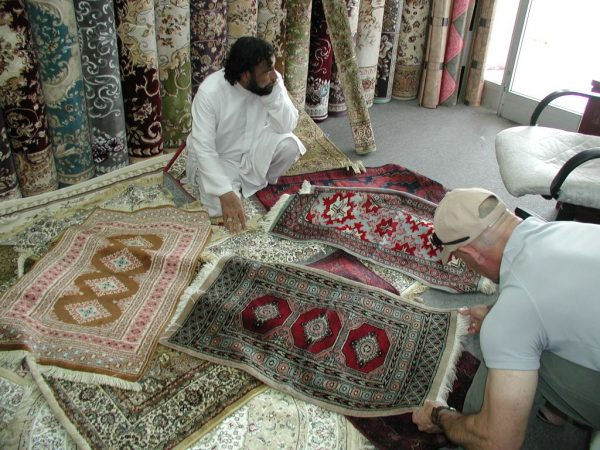 Looking at rugs in Abu Dhabi shop.
