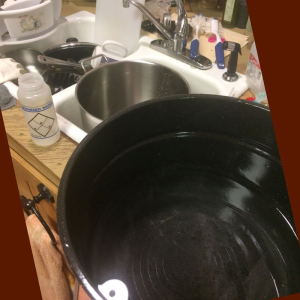 The large pot of heated water, the washing pot, and the dirty dishes that need to be pre-rinsed.
