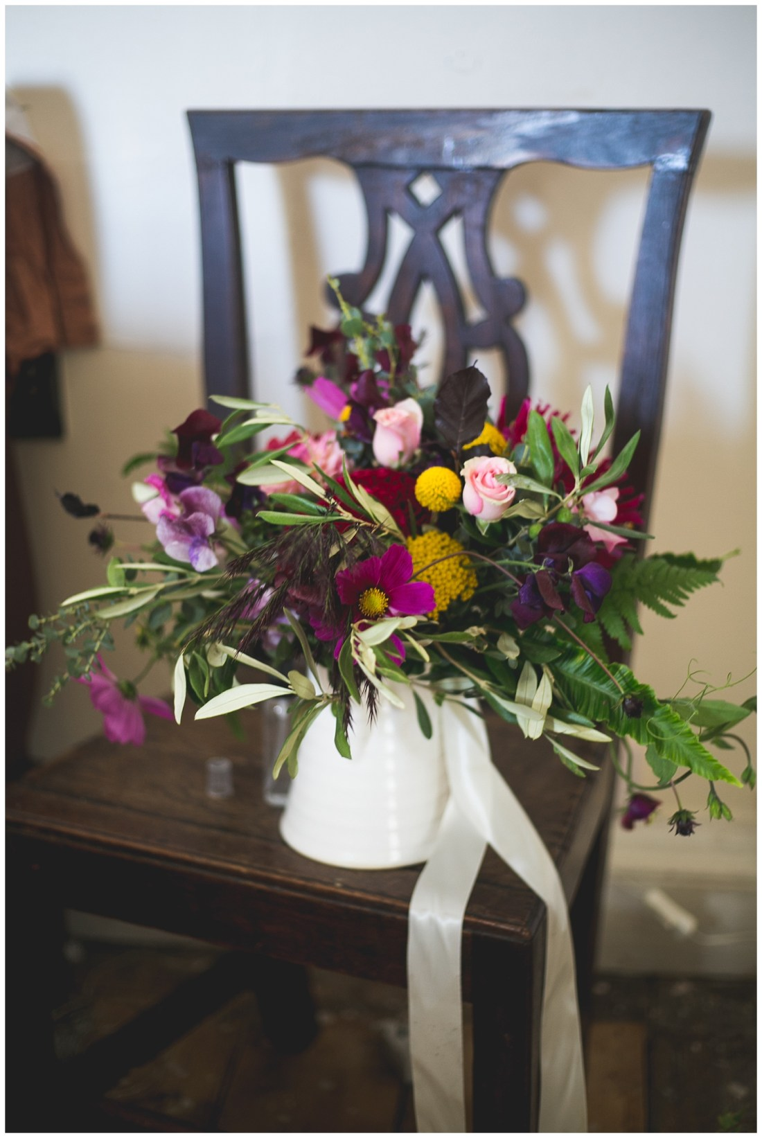 Wild rustic floral bouquet with pink roses, green leaves and purple accents