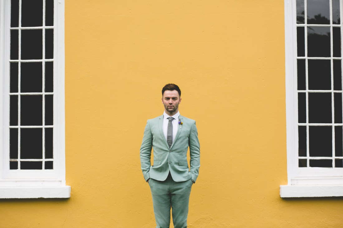 Wes Anderson Wedding with a groom in a pastel green suit