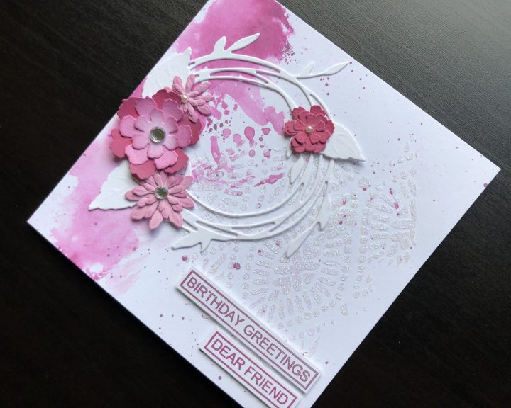 hand made birthday card with die cut wreath and flowers and stencilled glitter paste background