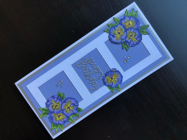 Hand made birthday card with die cut frame and apertures and stampcut pansies.