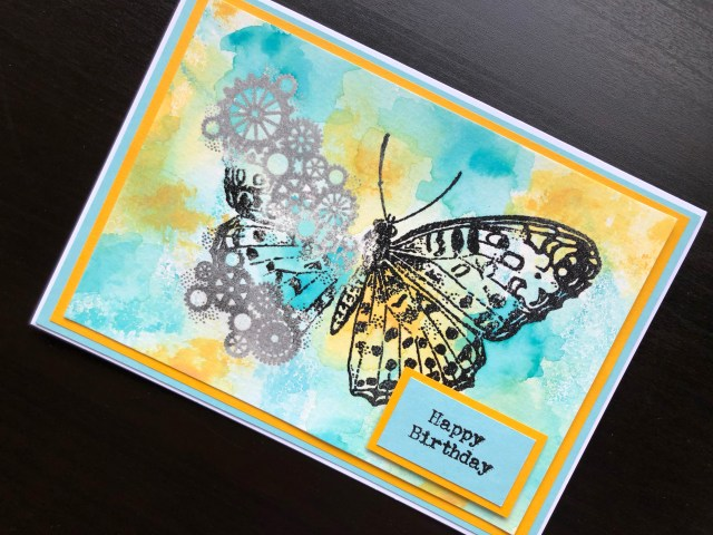 Hand made birthday card with stamped and embossed cog butterfly and inked background.