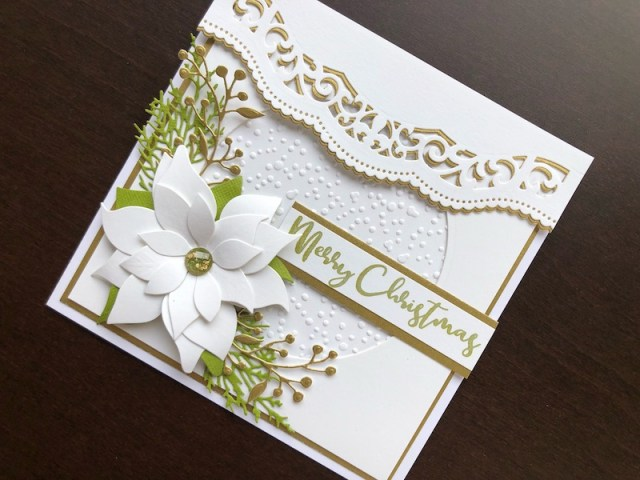 Hand made Christmas card with a white die cut poinsettia, embossed snowfall background and stamped greeting.