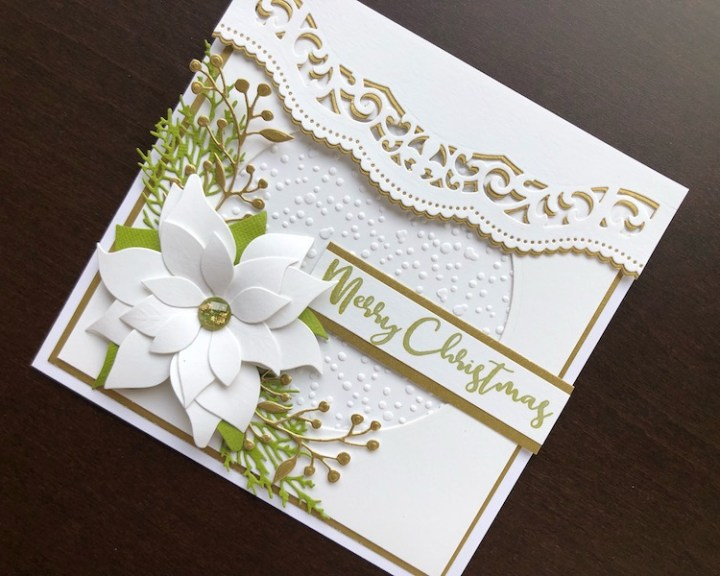 Hand made Christmas card with white die cut poinsettia and embossed snowfall background