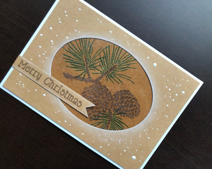 hand made Christmas card with stamped pine cones and heat embossed snowfall effect