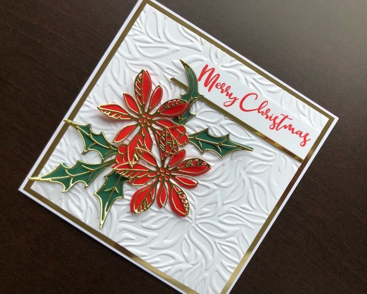 Hand made Christmas card with die cut layered poinsettia and holly on an embossed background
