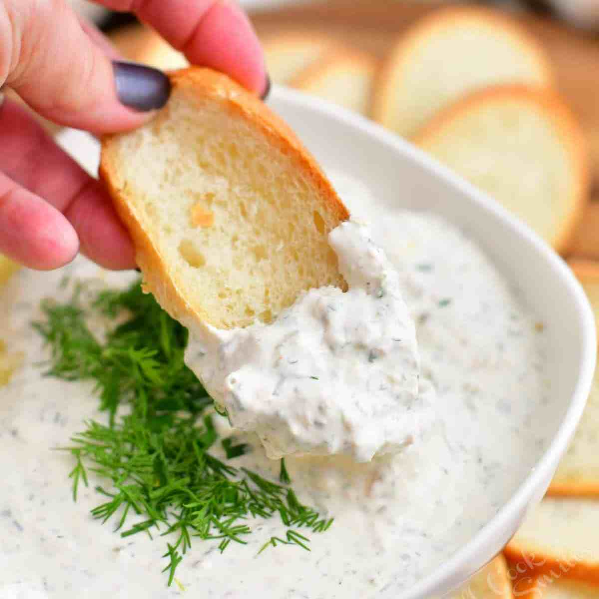 close up image: dipping toasted bread into bowl with salmon cream cheese dip
