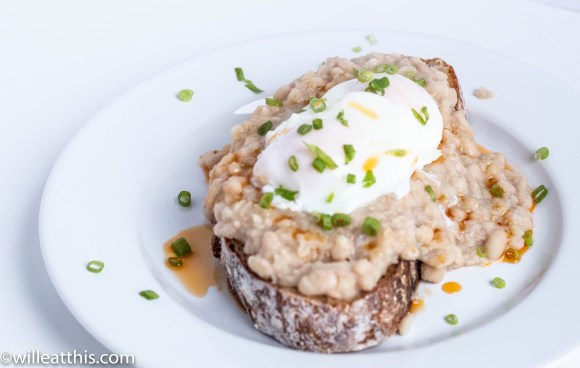 slice of noknead bread with mashed white beans and poached eggs