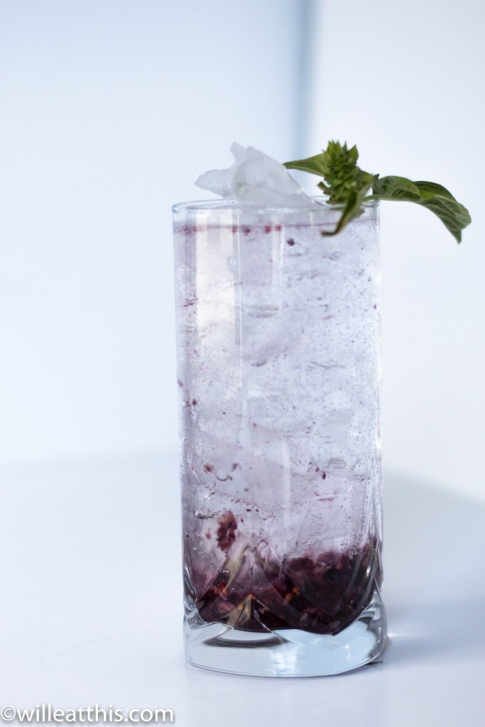 a glass cup with smash blackberry on the bottom. the glass is filled with ice and sparkling water. A sprig of basil sits on the rim.